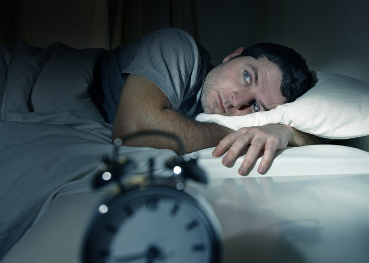 young man in bed with eyes opened suffering insomnia and sleep disorder thinking about his problem
