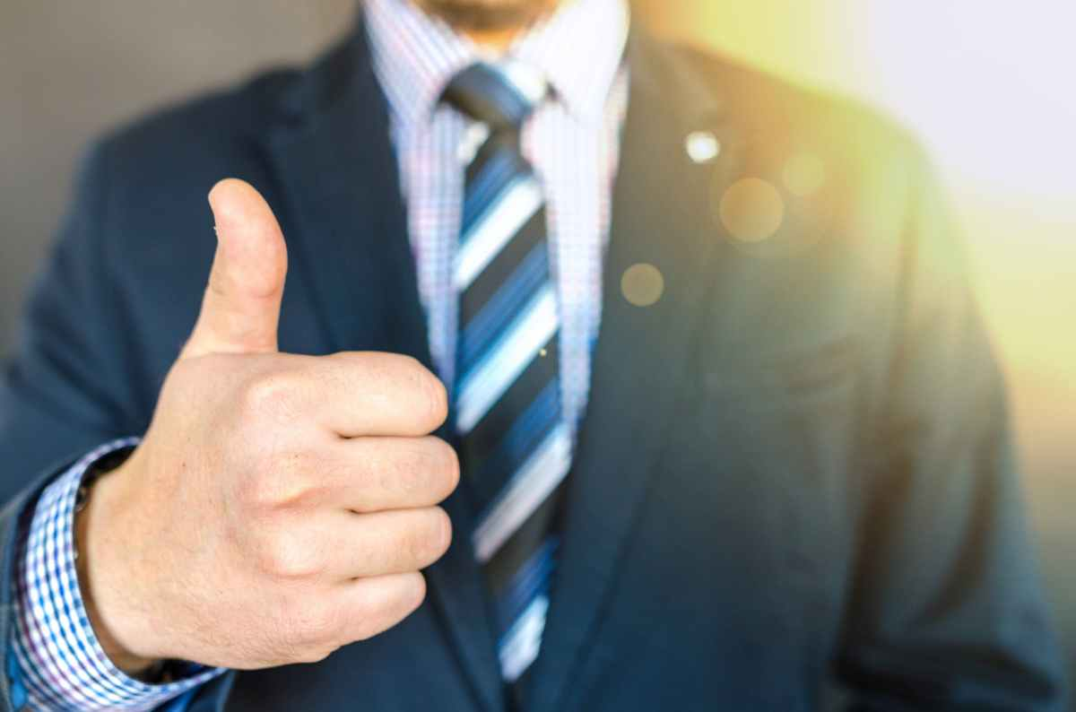 close up photo of man wearing black suit jacket doing thumbs up gesture