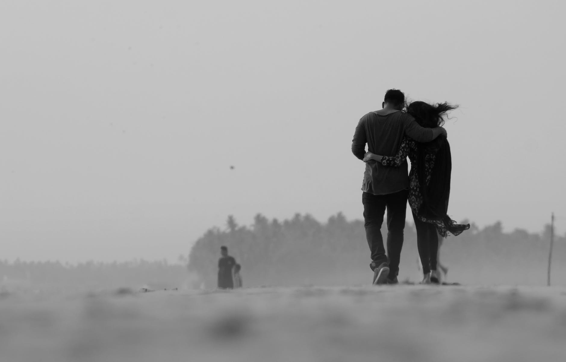 grayscale photography of couple walking on ground