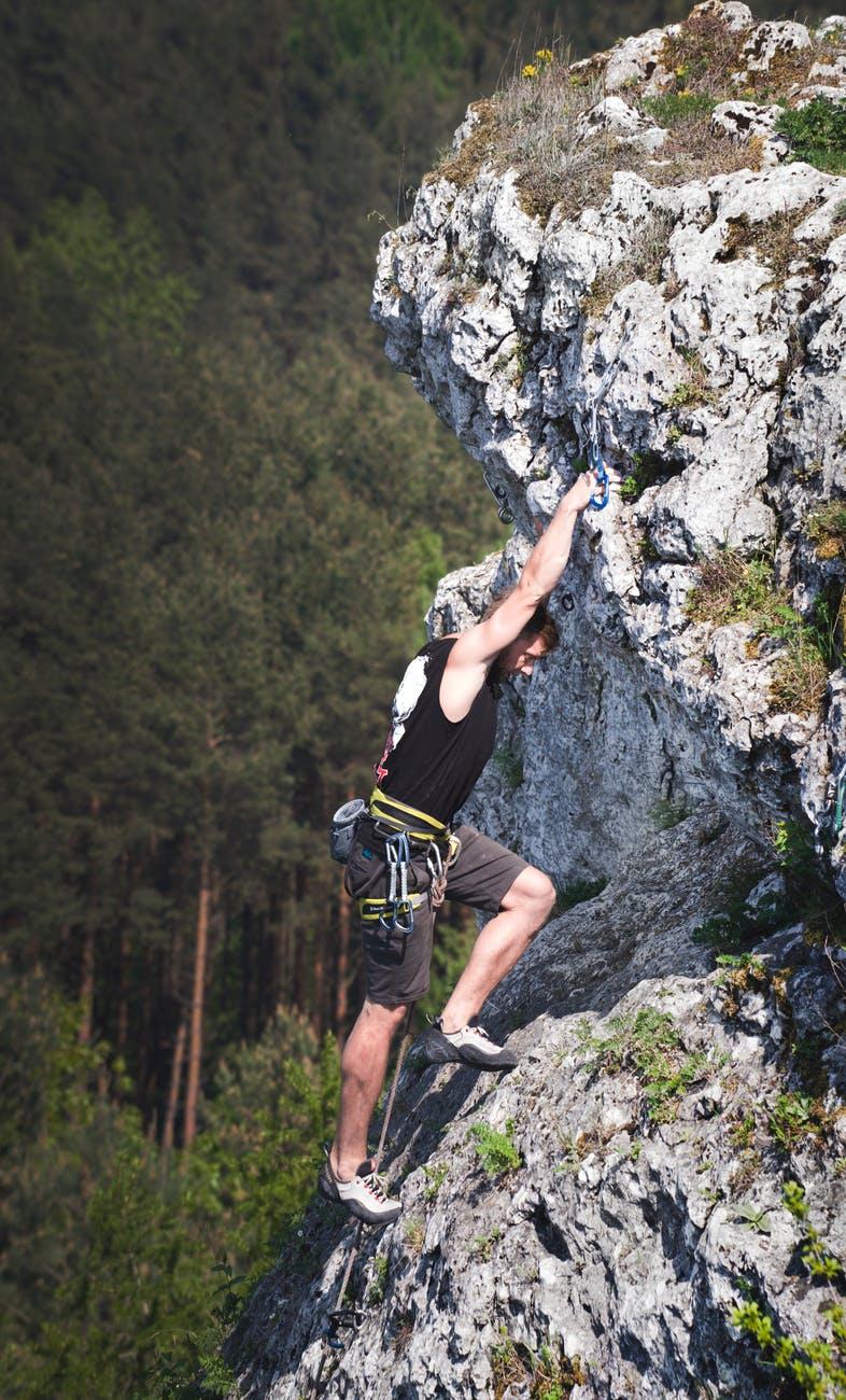 man wearing black tank top and brown shorts climbing rock