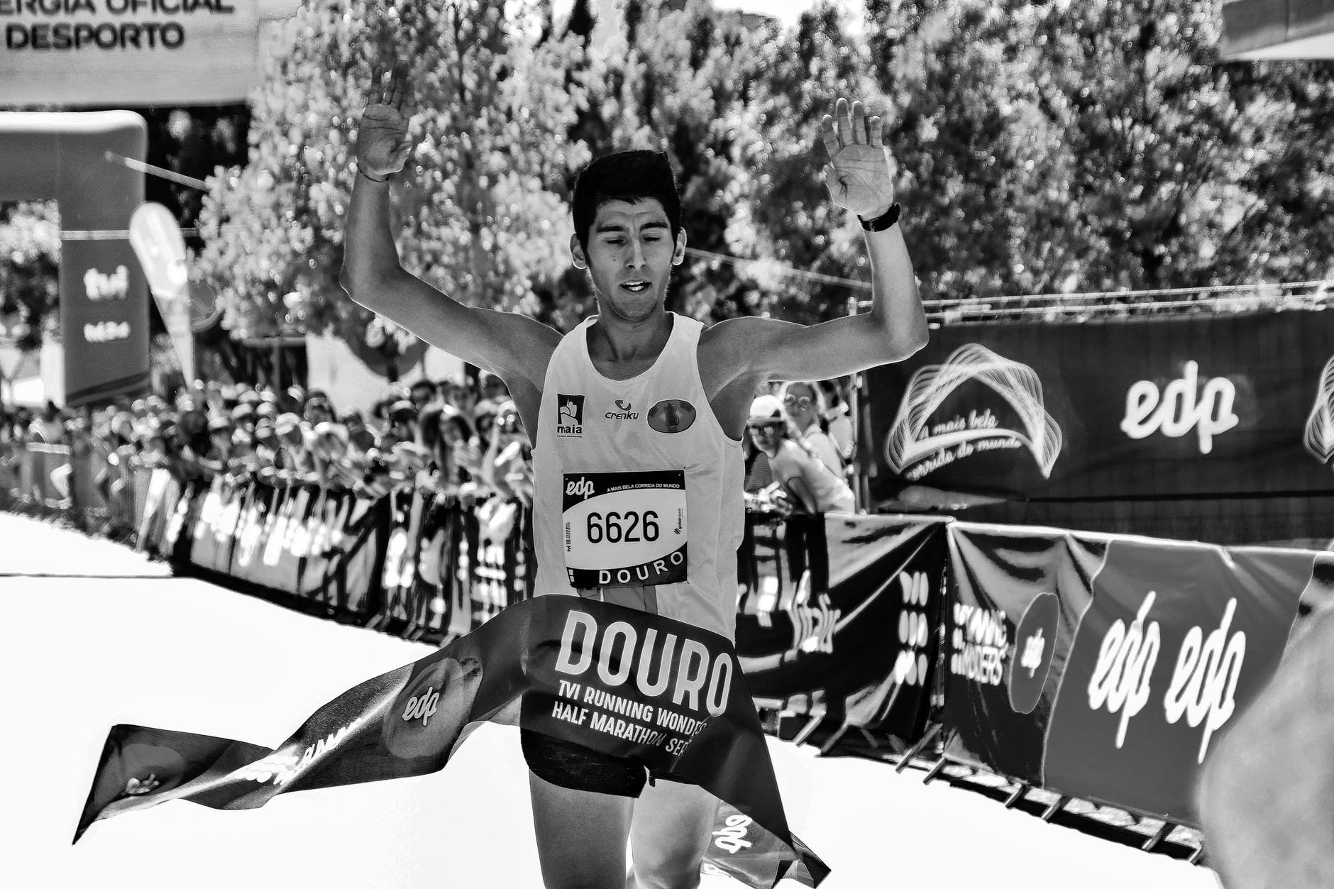 grayscale photo of man at the finish line of a marathon race