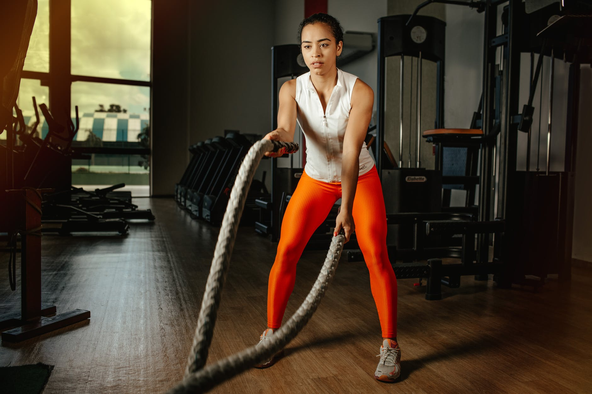 woman holding two ropes in gym